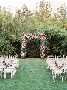 Lovely trellis decorated with flowers and greenery for a backyard wedding ceremony. White Chiavari chairs embellished with floral  garland. Get more ideas on our blog.   #weddinginspiration #weddingblogger #weddingideas #weddingblog #weddingdesign #weddingidea #weddingdecoration #weddingdetails #weddingstyle #weddingdecor