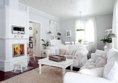 Romantic pure white living room. Its centerpiece is a white Katrilli fireplace with bread oven by Uunisepät from Finland.