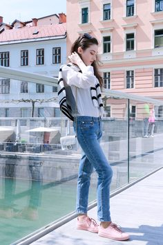 Fashion blogger Veronika Lipar of Brunette From Wall Street standing on the bridge dressed in light blue jeans, pale pink sneakers, black and white striped top, and white mini bag