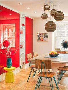 ameublement salle à manger avec un mur d'accent rouge, des chaises en bois à piétement en épingle et suspensions boules