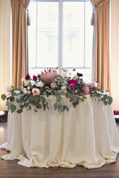 Lush Protea Centerpieces and Sweetheart Table | Parsonage Events https://www.theknot.com/marketplace/parsonage-events-clarkston-mi-219748 | Heather Saunders Photography https://www.theknot.com/marketplace/heather-saunders-photography-royal-oak-mi-167338