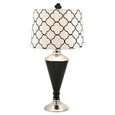 Crafted of glass with an iron base, this table lamp features a white drum shade with a quatrefoil motif.   Product: Table lamp
