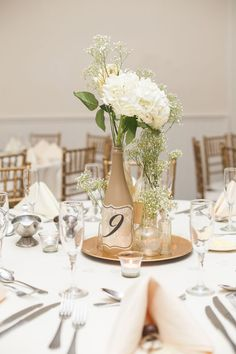 DIY wine bottle centerpiece with hydrangeas and blush roses. #tablestyling #decoratedwinebottles
