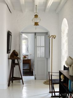 A cool palette of gray and white defines the interior spaces. Nineteenth-century ship's lantern; rope sculpture from Préface.
