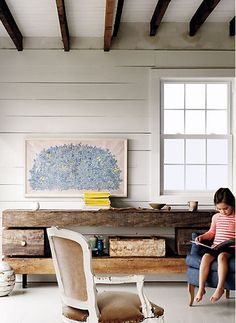 Love the white walls and uneven ceiling. also love the table, the art, the chair...and the darling little girl.