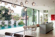 cuisine spacieuse et moderne avec îlot central fonctionnel, table en bois, chaises Eames blanches et suspensions boules