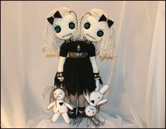 This tattered rag doll stands 22 inches tall, is completely hand stitched, has vintage button eyes, and yarn hair. Shes wearing a black tattered dress, a brown & black belt with pewter bats, black panties, black & white striped stockings, and black leather shoes.  Her accessories consist of two black chokers with pewter skulls, a pewter skull necklace, two leather studded wrist cuffs with skulls, rhinestone studs, and silver rings with spiders, matching black hair bows with pewter skulls…