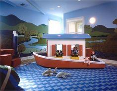 salle de jeux enfant décorée thème mer - un bateau de jeux, tapis bleu à motif ondes et papier peint paysage forestier