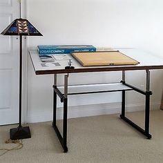 """Modern drafting table, portable drafting board, floor lamp, cutters. Adjustable drafting table 6W'x38""""Dx38""""H at front; drafting board (seen on table top). Modern metal floor lamp 61""""T with southwestern shade 18.5""""sq; mat cutters & manuals (seen on table top). All pcs very good condition"""