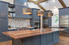 Contemporary kitchen with dark blue cabinets, large island with wood counter and bronzed drum pendant lights
