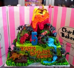 Square Vanilla pound cake iced in green butter icing, with 3D Wicked Chocolate Volcano on top, piped jungle scene with toy dinosaurs