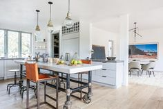Leather bar stools in white kitchen with industrial kitchen island