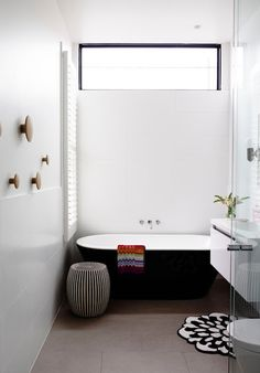 Austin design bathroom with black bath and Muuto dots