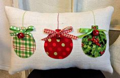 This lovely colorful Christmas pillow is a great addition to any holiday decor. It is made with ivory burlap and embellished with three round Christmas balls in reds and greens. This pillow measures approximately 15x8 inches and is fully lined and nicely stuffed with soft polyfill. The ornaments are accented with red jingle bells and coordinating ribbons. There is matching thread that comes down from the top of the pillow and to the top of the ball ornament to give a look like they are…