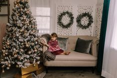 holiday mini session photo shoot christmas toddler girl looking at ornaments neutral greenery garland tree lights screen sofa couch magic