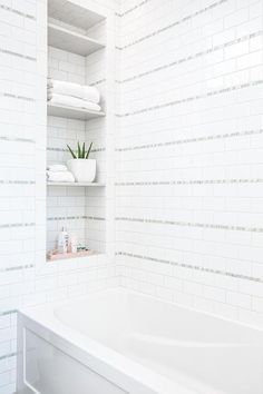 A drop-in wainscot bathtub is fixed against white subway backsplash tiles accented with gray glass tiles and beneath a tiled niche fitted with stacked shelves. Subway Backsplash, Glass Tile Accent, White Bathroom Tiles, Bathtub Tile, Small Bathroom Decor, Grey Glass Tiles, Transitional Bathroom, Bathrooms Remodel, Bathroom Design