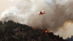 Flames of the Waldo Canyon fire race down into western portions of Colorado Springs, Colo. on Tuesday. A helicopter tries to slow it down before it left a trail of destruction, burning homes and buildings in it's path. Heavily populated areas in the fire's path have been affected.