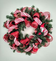 Need to add a little holiday cheer to your day? This traditional wreath with a cute little snowman and glittery pine cones will fit the bill! Made of traditional pine like greenery wreath form with red deco mesh ribbon and candy cane striped ribbon. Approximately 18 inches in diameter. Includes a metal hanger on the back of the wreath that should easily fit onto a wreath or picture hanger. Item is ready to ship!  Wreath should be protected from the elements such as snow, wind, and rain so…