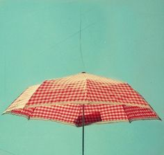 red and white checkered patio umbrella against a completely blue sky