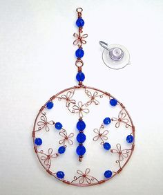 This small round flower suncatcher is handmade with cobalt blue glass beads and copper wire.    This window art measures 8 (20.3 cm) in length. The