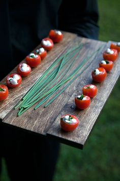 "Caprese salad is made miniature, with mozzarella ""perle"" served in cherry tomato halves."