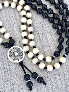 The karma pendant concentrates positive energy and strengthens the sensory organs. The combination of black and white enhances inspiration, purification and protection against negativity. Black and white wood mala necklace -108 (64 black, 44white) round Czech wooden beads 10mm knotted,