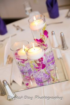 Glass cylinders filled with orchids and floating candles