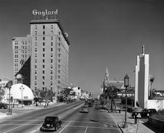 This is Wilshire Boulevard in 1936. The Brown Derby, the entrance to the Ambassador Hotel, the Gaylord Apartments, and, in the far distance, the tower of the Bullock's Wilshire department store are all visible.