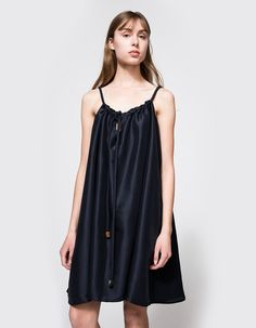 From Delfina Balda, a modern drawstring dress in Navy. Features gathered neckline with keyhole detail, coordinating drawstring with handmade horn aglets, in seam pockets, oversized silhouette and a a generous one-size-fits-all construction. Hits above the