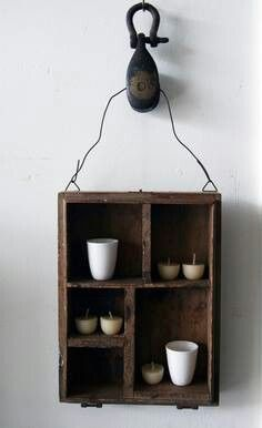 Vintage crate used as hanging wall shelf. Secured with wire through an old pulley. Need this small one!!!