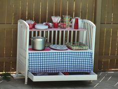 Outdoor entertaining is a breeze with this recycled baby crib as a serving table on wheels!  This needed lots of weather resistant paint and can be decorated for other themes.