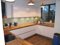 This kitchen transformation has created the perfect living space for a busy family house. With high gloss white cabinets topped with solid wood worktops. The customer added a subtle hint of colour with light green tile splashbacks, #German #Kitchens #HighGloss #White #WoodenTops #Handleless #Copper #Neff #Appliances