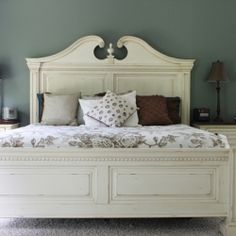 A cream colored bed stands out with flare against the deep blue/green colored walls. Paint is Sherwin Williams Retreat.