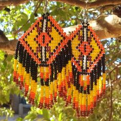 Brinco de miçanguinhas feito artesanalmente. Cores predominantes: amarelo, laranja e preto. Efeito tapeçaria.