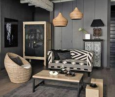 deco salon gris, murs couleur anthracite, canapé en noir et blanc, fauteuil en rotin, table basse en bois et suspensions design intéressant