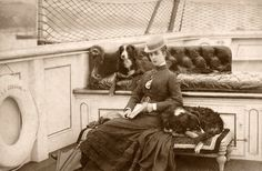 Victorian Lady with her two dogs on a ship or boat of some kind (river in back ground) and Lifesaver to left of photo.  Looks like she has an umbrella laying beside her, so i assume the trip is a long one....fascinating. would love to know so much more about what this is about!!!!