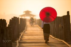 Unidentified Burmese woman walking on U Bein Bridge - Unidentified Burmese woman holding traditional red umbrella and walking on U Bein Bridge during warm light of sunrising time. Unidentified Burmese woman walking on U Bein Bridge by Anusorn Sutapan - Photo 139785391 - 500px.  #sunrise #red #girl #umbrella #travel #bridge #beautiful #gold #woman #wood #warm #asia #walking #bagan #burma #myanmar #clothes #asian #traditional #burmese #woodenbridge #ubeinbridge #mandalay
