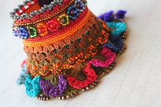 https://flic.kr/p/oANLhM | Watsonia Latifolia: freeform crochet cuff with brown, orange, olive green, blue and red beaded crochet flowers and lace by irregularexpressions