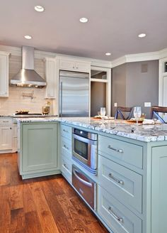 Bright and light. Warm wood floors, white cabinets and walls, with light blue cabinets in the island.