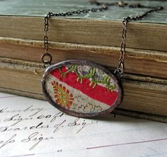 Crazy Quilt Necklace: A rescued piece of vintage crazy quilt sits between two sheets of micro-thin glass, soldered together with a silver solder and finished with an antiqued patina.