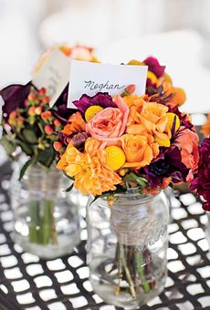 Before the ceremony, mason jars hold the bridesmaid bouquets of yellow and peach roses and dahlias