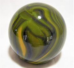 Vintage hand blown art glass paper weight Various shades of olive green and yellow, on a transparent blue base, but you can only see this when held up to the light About 3 inches diameter Unsigned I see only one hard to find miniscule mark Ground and polished bottom Very good vintage condition  International buyers welcome 30817  Credit Cards and Paypal accepted