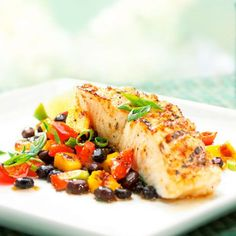 Sea bass is a firm fish that fares well on the grill. Grilled mango and bell pepper add a subtle smokiness to the colorful black bean salad.