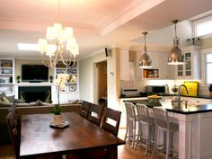 Maximize living space by combining, where possible, your kitchen and dining room. Here, six chairs are arranged around a large dining table on which a white orchid is used as a centerpiece. In the adjacent black and white kitchen, stainless accents like the pendant lights and barstools give the kitchen a sleek, contemporary feel.