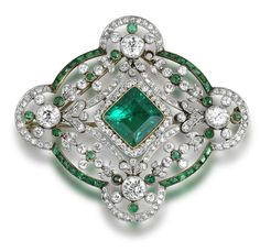 A belle époque emerald and diamond brooch/pendant, circa 1910.  Set to the centre with a square-cut emerald and single-cut diamond cluster, to an openwork border set with swags and floral garlands, within a quatrefoil frame, millegrain-set throughout with single and brilliant-cut diamonds and calibré and circular-cut emeralds, diamonds approximately 4.80 carats total, detachable brooch fitting, one emerald deficient, length 5.2cm