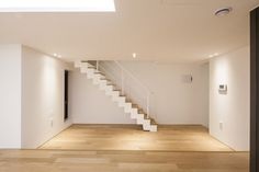 white empty living room with stair, wood floor, window, pendant lighting.