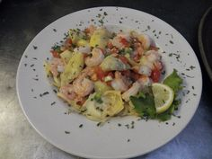 AMI PASTA!  A divine mixture of large shrimp poached in a white wine garlic sauce, artichoke hearts, tomatoes, scallions and herbs served over a delicious bed of linguine!