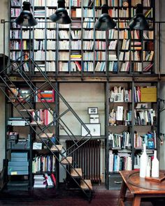 I like the idea of one very tall (two story?) wall being used as a library wall by creating a stair and porch to reach the upper shelves on the wall. Great idea! Just needs a seat on top level.
