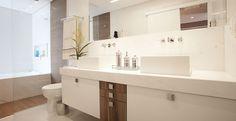 o banheiro do casal ganhou glamour com banheira e netais. Os enfeites sobre a bancada são delicados. O tapete combina com as gavetas em madeira com puxadores metálicos.