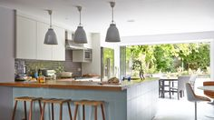 Pendant lights are a great way to highlight certain areas of a room and work perfectly above this breakfast bar in this open-plan kitchen